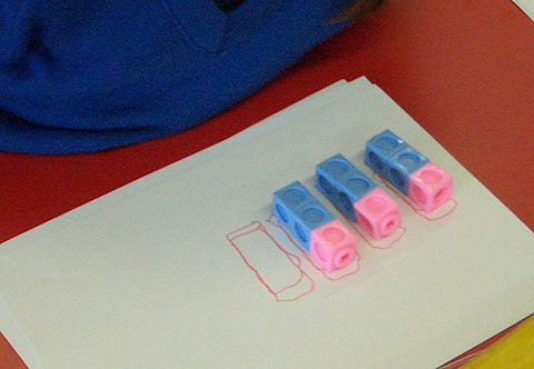 Three trains of coloured cubes, each train with two blue cubes and one pink, aligned with the pink cube at the top in all trains.