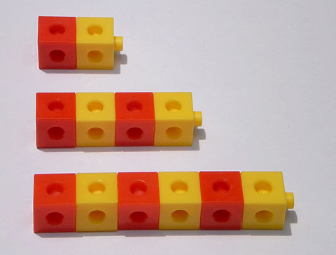 Three groups of cubes alternating in colour between red and yellow. The groups grow by two each time, starting with two cubes.