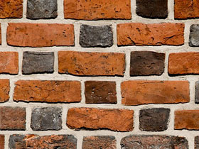 A brick wall with each row alternating short and long bricks.